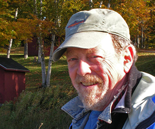 photograph of john copley, the artist, standing in wooded area with red buildings in the background